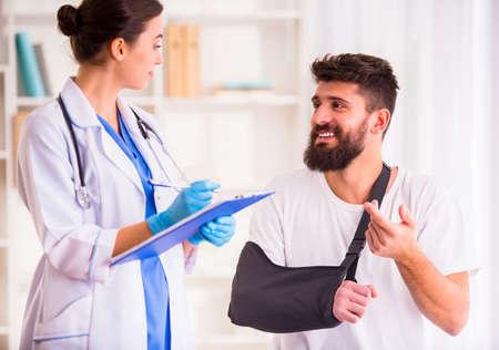 Foto de Injury hands. Young man with injured hands. Young woman doctor helps the patient - Imagen libre de derechos