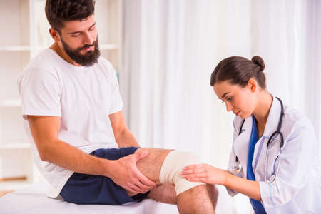 Photo pour Injury leg. Young man with injured leg. Young woman doctor helps the patient - image libre de droit