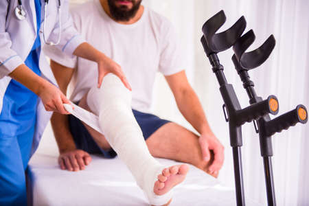 Photo for Injury leg. Young man with injured leg. Young woman doctor helps the patient - Royalty Free Image