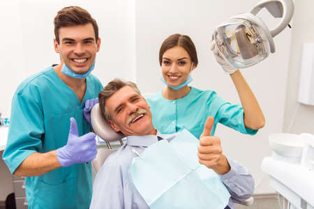 Photo for Young doctor dentist and his assistant, elderly patient showing thumb up, smiling and looking at the camera - Royalty Free Image