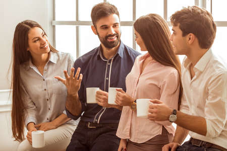 Foto de Coffee break chat. Group of attractive business people, standing next to each other, holding a cups, smiling standing at the window - Imagen libre de derechos