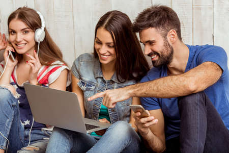 Photo for Group of attractive young people sitting on the floor using a laptop, Tablet PC, smart phones, headphones listening to music, smiling - Royalty Free Image