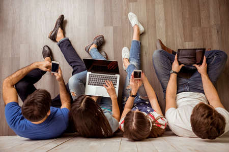 Photo pour Group of attractive young people sitting on the floor using a laptop, Tablet PC, smart phones, headphones listening to music, smiling - image libre de droit