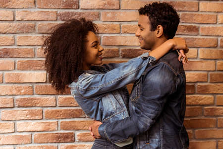 Photo pour Side view of young attractive Afro-American couple hugging, looking in camera and smiling while standing against brick wall - image libre de droit