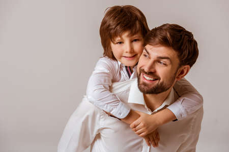 Photo for Portrait of a handsome father carrying his cute son on back and smiling. Both in white classical shirts standing on a gray background. - Royalty Free Image