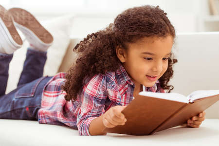 Foto de Cute little Afro-American girl in casual clothes reading a book and smiling while lying on a sofa in the room. - Imagen libre de derechos