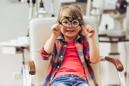 Foto de Little boy looking at camera and smiling while sitting on chair at the ophthalmologist - Imagen libre de derechos