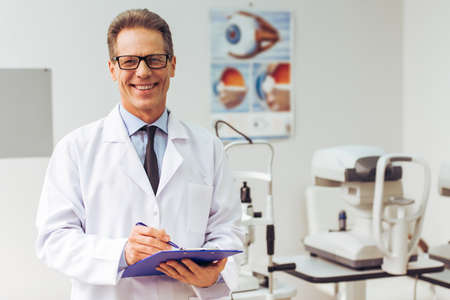 Foto de Handsome middle aged ophthalmologist making notes and smiling while standing in his office - Imagen libre de derechos