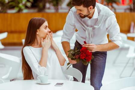 Photo pour Handsome man with bunch of red roses and wedding ring proposing to his beautiful woman in cafe - image libre de droit