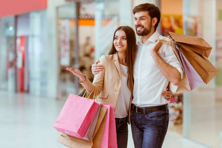 Photo for Happy beautiful young couple holding shopping bags, looking upon showcase and smiling while standing in mall - Royalty Free Image