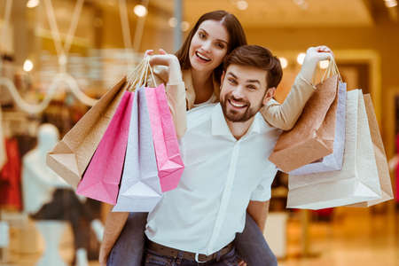 Photo pour Happy beautiful young couple holding shopping bags while standing in mall. Woman pickaback - image libre de droit