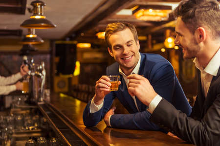 Photo for Two young businessmen in suits are smiling and clanging glasses of alcoholic beverage together while sitting at bar counter in pub - Royalty Free Image