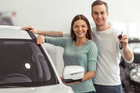 Foto de Beautiful young couple is smiling and looking at camera while leaning on their new car in a motor show. Man is holding car keys - Imagen libre de derechos