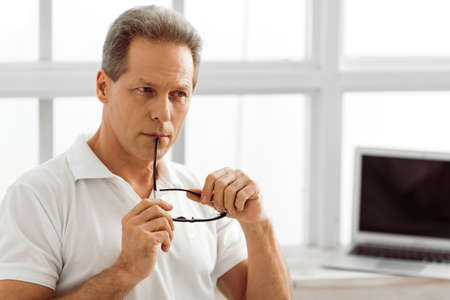 Foto de Thoughtful middle aged man is holding eyeglasses and thinking while sitting near the window at home, laptop in the background - Imagen libre de derechos