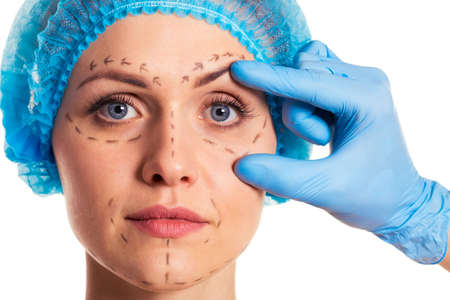 Foto de Beautiful woman in medical headwear with sketches on face, surgeon in medical gloves is examining her face, isolated on a white background - Imagen libre de derechos