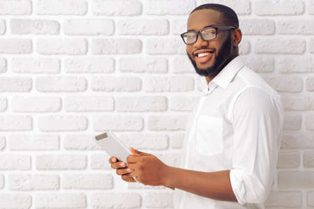 Photo pour Side view of Afro American man in classic shirt and glasses using a tablet, looking at camera and smiling, standing against white brick wall - image libre de droit