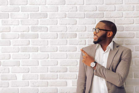 Photo for Handsome Afro American man in classic suit and glasses is smiling, looking and pointing away, against white brick wall - Royalty Free Image