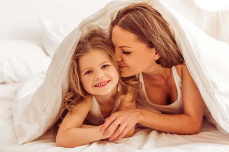 Photo pour Beautiful young mother is kissing her daughter in cheek, lying in bed under the blanket. Little girl is looking at camera and smiling - image libre de droit