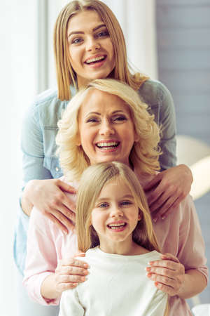 Photo pour Portrait of three generations of happy beautiful women looking at camera, hugging and smiling - image libre de droit