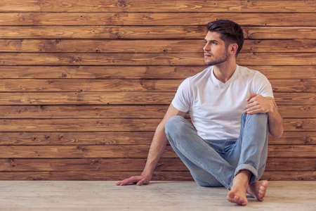 Foto de Handsome pensive young man is looking away and thinking, sitting on floor against wooden wall - Imagen libre de derechos