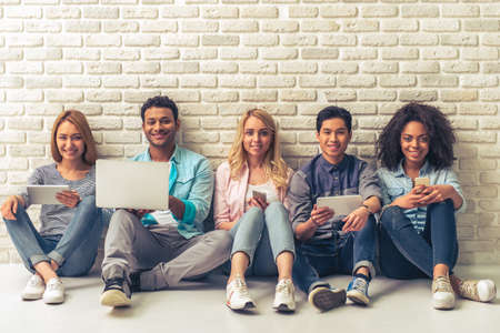 Photo pour Beautiful young people of different nationalities are using gadgets, looking at camera and smiling, sitting against white brick wall - image libre de droit