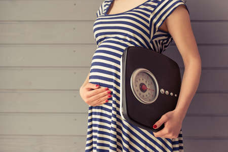Foto de Cropped image of beautiful pregnant woman holding weigh scales and keeping one hand on a belly, standing against gray wall - Imagen libre de derechos