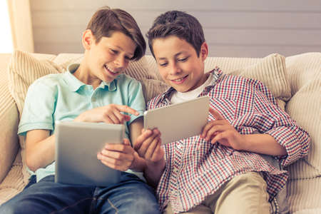 Photo pour Two attractive teenage boys are using tablets, talking and smiling while sitting on the couch at home - image libre de droit