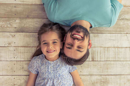 Foto de Top view of handsome young father and his cute little daughter looking at camera and smiling, lying on wooden floor - Imagen libre de derechos