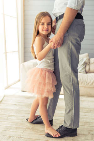 Photo for Cropped image of young father and his cute little daughter dancing at home. Girl is standing on her father's feet, looking at camera and smiling - Royalty Free Image