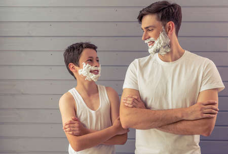 Foto de Handsome young father and his teenage son with shaving foam on their faces are looking each other and smiling, standing cross-armed against gray wall - Imagen libre de derechos