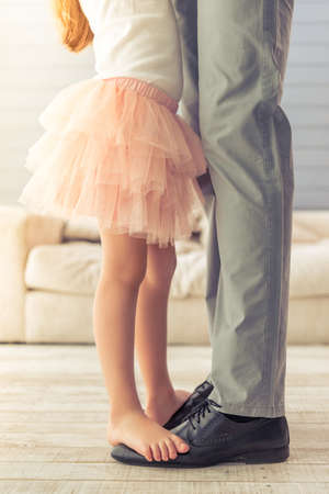 Foto de Cropped image of young father and his cute little daughter dancing at home. Girl is standing on her father's feet - Imagen libre de derechos