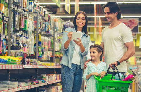 Foto de Beautiful young parents and their cute little daughter are smiling while choosing school stationery in the supermarket. Mom is making notes in the list - Imagen libre de derechos