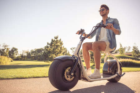 Foto de Handsome stylish man is smiling while riding on the electric scooter in the park - Imagen libre de derechos