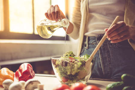Photo pour Cropped image of beautiful young girl mixing salad while cooking in kitchen at home - image libre de droit