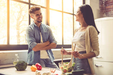 Photo for Beautiful young couple is talking, looking at camera and smiling while cooking in kitchen at home. Woman is mixing salad - Royalty Free Image
