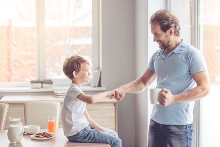 Foto de Father and son are giving five and smiling while having a snack in kitchen - Imagen libre de derechos