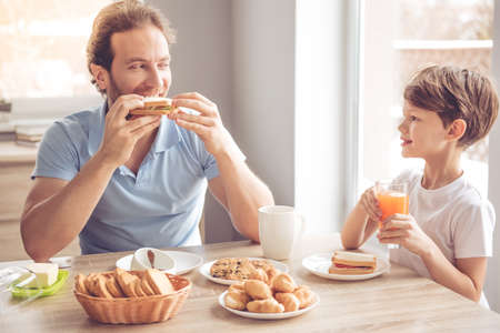 Photo for Father and son are talking and smiling while having a breakfast in kitchen - Royalty Free Image