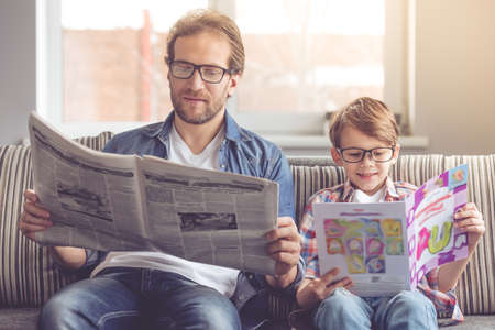 Photo for Father and son are reading newspapers and smiling while spending time together at home - Royalty Free Image