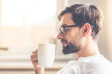 Foto de Handsome man in eyeglasses is smelling the aroma of coffee and smiling while resting at home - Imagen libre de derechos