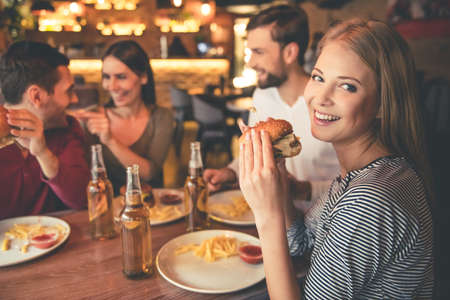 Photo for Happy friends are eating burgers, talking and smiling while spending time together in cafe - Royalty Free Image