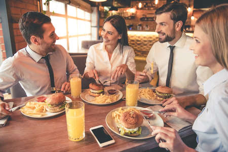 Photo pour Business people are eating, talking and smiling while having lunch in cafe - image libre de droit