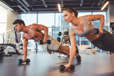 Photo for Attractive young sports people are working out with dumbbells in gym - Royalty Free Image
