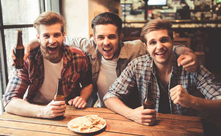Handsome friends are drinking beer, looking at camera and smiling while resting at the pub