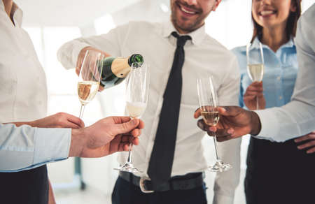 Photo for Cropped image of successful business people drinking champagne, talking and smiling while celebrating in office - Royalty Free Image