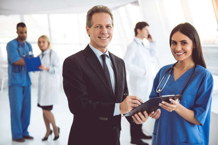Photo pour Handsome mature businessman and beautiful young doctor are looking at camera and smiling while standing in the hospital hall - image libre de droit