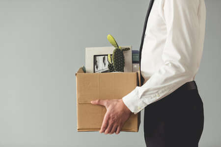 Foto de Getting fired. Cropped image of handsome businessman in formal wear holding a box with his stuff, on gray background - Imagen libre de derechos