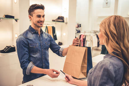 Photo for Handsome shop assistant is smiling while giving purchases and credit card to beautiful client - Royalty Free Image