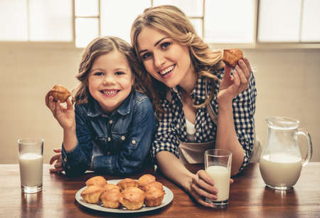 Photo for Cute little girl and her beautiful young mom are eating muffins with milk, looking at camera and smiling while resting at home - Royalty Free Image