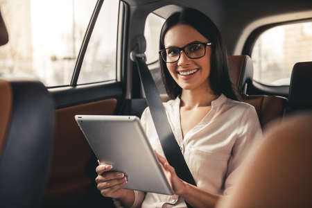 Photo pour Beautiful business woman in eyeglasses is using a digital tablet and smiling while sitting on back seat in the car - image libre de droit