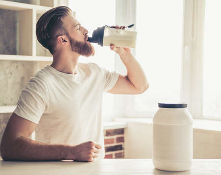 Foto de Handsome young bearded sportsman is drinking while preparing sport nutrition in kitchen at home - Imagen libre de derechos